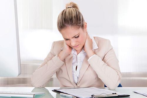 женщина сидит за столом и держится за шею