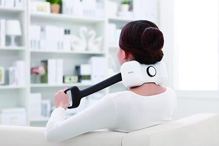 женщина с электромассажером на шеи сидит на кресле