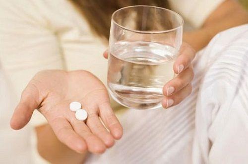 таблетки и стакан воды в руках