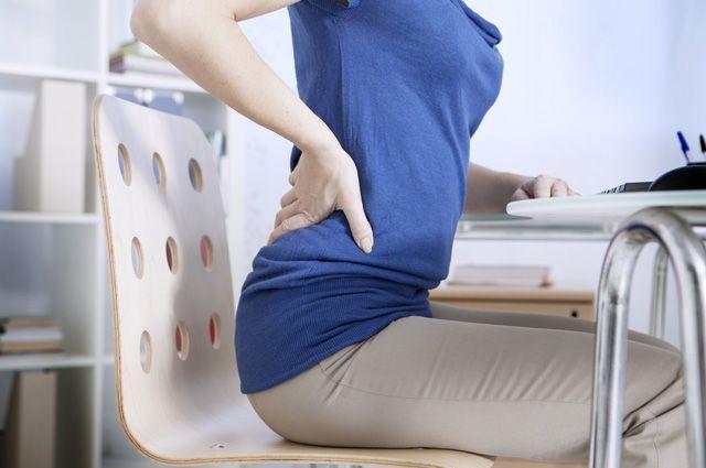 женщина сидит на стуле и держится за спину