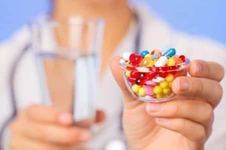 медикаменты и стакан воды в руках у врача