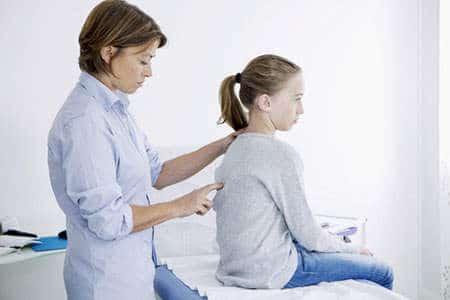 доктор осматривает спину девочки