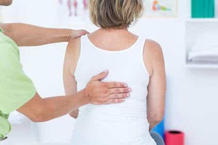 врач осматривает спину женщины