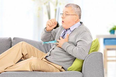 мужчина сидит на диване и кашляет