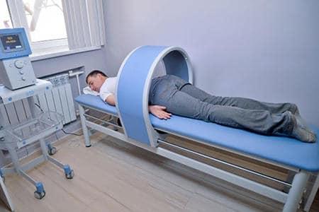 мужчина лежит на кушетке под аппаратом для проведения процедуры