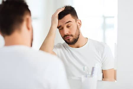 мужчина перед зеркалом держится за голову