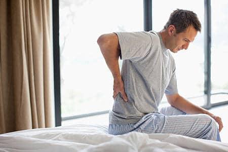 мужчина сидит на кровати и держится за спину