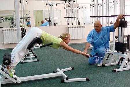 врач проводит занятие в спортзале с девушкой